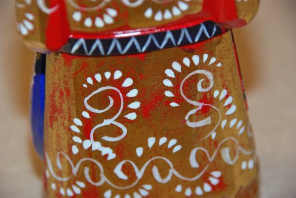 White paint details on a gold and red St. Nicholas Christmas Figurine