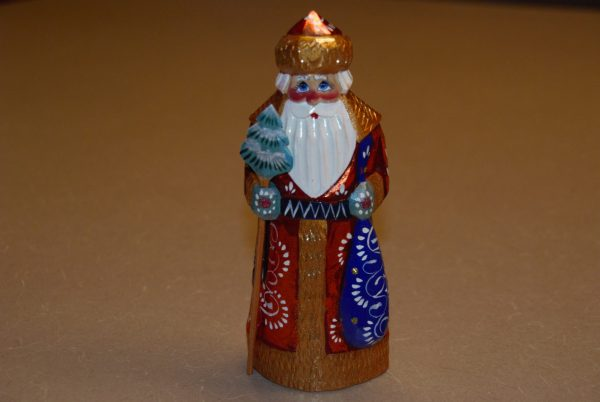 St. Nicholas figure holding blue sack and staff with tree