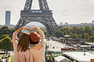 Two women making a heart with their arms in front of the Eiffel Tower